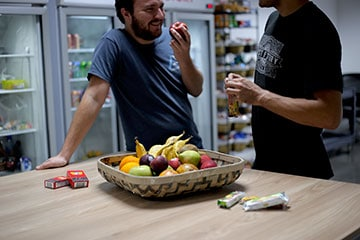 Two employees in front of a fruit basket in the office kitchen