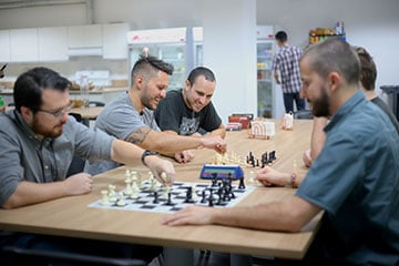 A group of men playing chess in the office kitchen