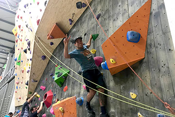 A man climbing a rock wall and smiling