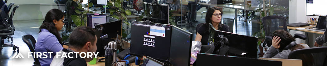 Image with software developers at a long work station with computer screens and laptops